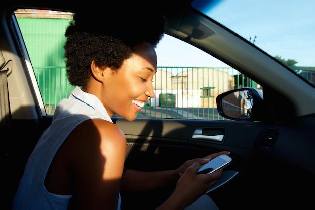 Femme africaine joyeuse à l'aide de téléphone portable dans une voiture