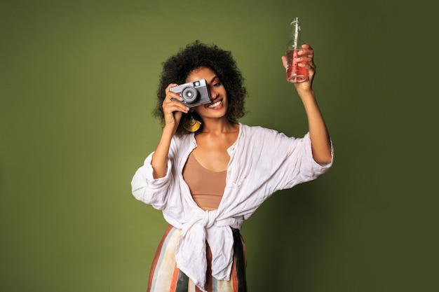 Femme africaine ludique avec maquillage élégant et coiffure faisant des photos et buvant un cocktail rose de paille.