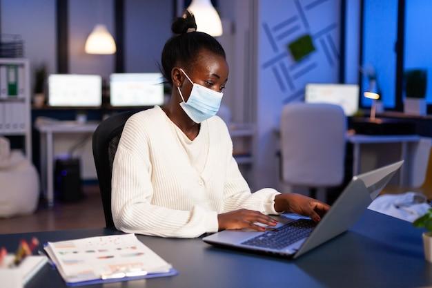 Femme africaine avec un masque facial lisant des e-mails tard dans la nuit pour respecter la date limite du projet travaillant dans un nouveau bureau commercial normal, analysant des documents, faisant des heures supplémentaires de stratégie pendant la pandémie mondiale