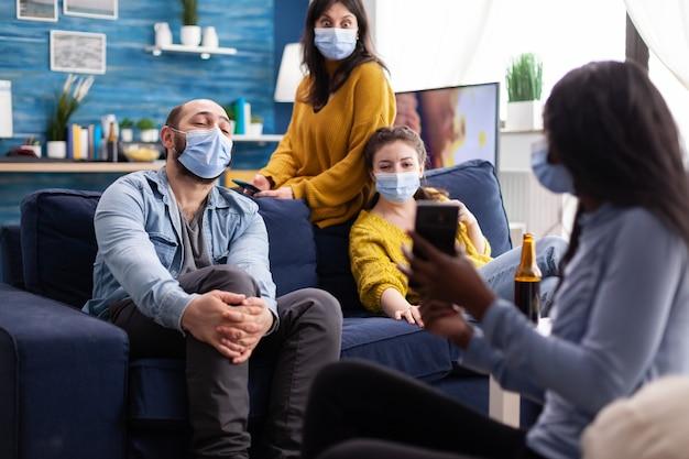Femme africaine montrant un clip amusant sur un smartphone traînant dans le salon de la maison portant un masque facial empêchant le coronavirus pendant la pandémie mondiale en maintenant une distance sociale.