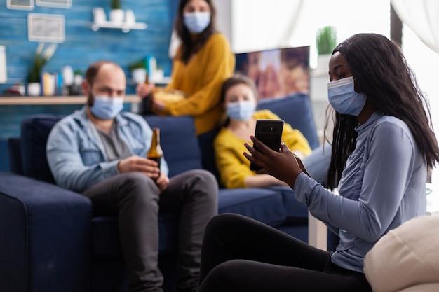 Femme africaine montrant à ses amis une vidéo amusante sur un smartphone portant le visage comme prévention contre covid19 pendant la pandémie mondiale en gardant une distance sociale avec un masque facial.