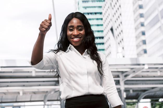Femme africaine montrent thump up sur fond d'immeuble de bureaux