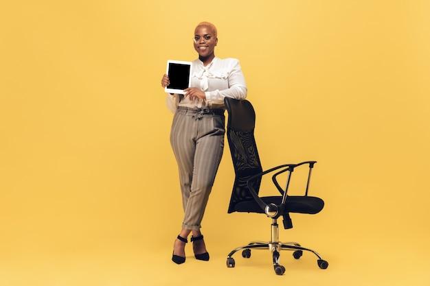Femme africaine sur mur jaune, copyspace