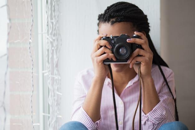 Femme africaine photographiant à la maison