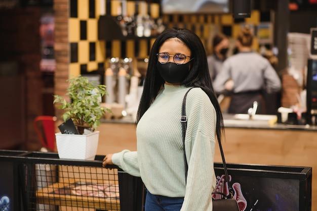 Femme africaine portant un masque médical jetable. shopping au supermarché pendant l'épidémie de pandémie de coronavirus. temps épidémique.