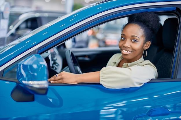 Femme africaine satisfaite au volant de l'automobile bleue représentée dans la salle d'exposition de voitures