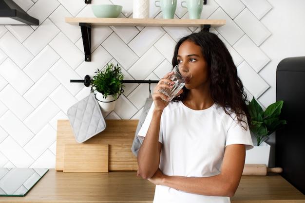 Femme africaine se dresse sur la cuisine et boit de l'eau