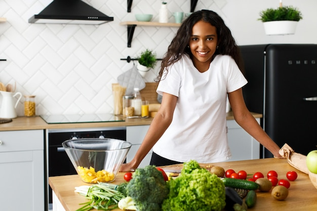 Femme africaine se tient devant un bureau de cuisine avec différents fruits et légumes