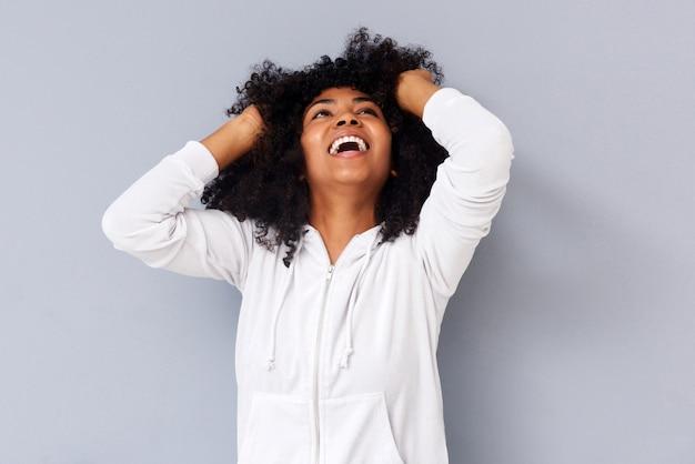 Femme africaine souriante avec les mains dans les cheveux sur fond gris
