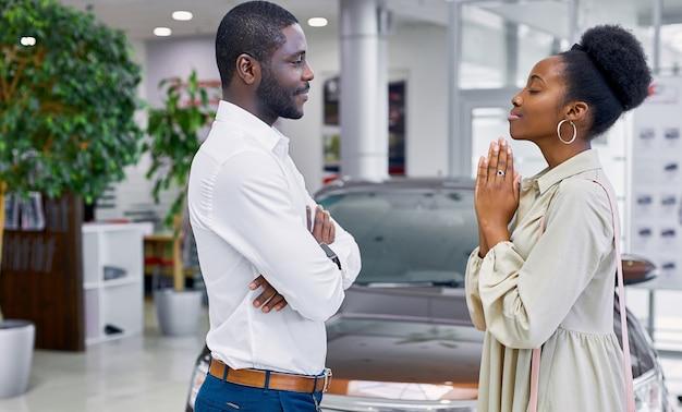Femme africaine suppliant son mari dans la salle d'exposition de voiture