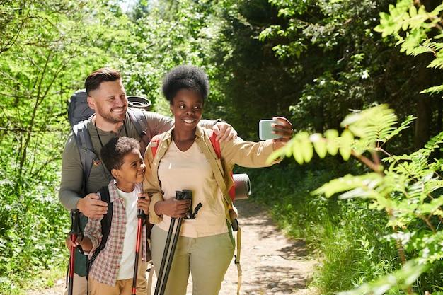 Femme africaine tenant un téléphone mobile et faisant le portrait de selfie de sa famille pendant leur voyage dans la forêt