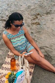 Femme africaine vérifiant son téléphone portable assis sur la plage
