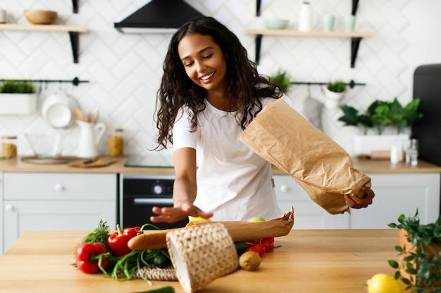 Une femme afro affiche des produits d'un sac en papier sur la table