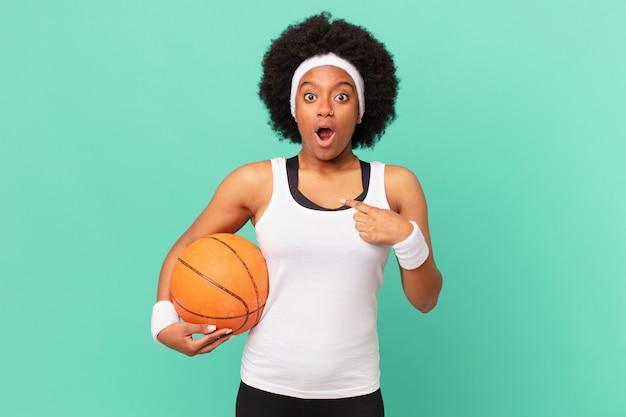 Une femme afro a l'air choquée et surprise avec la bouche grande ouverte, pointant vers soi. concept de basket-ball