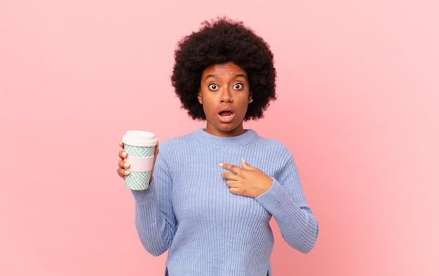 Une femme afro a l'air choquée et surprise avec la bouche grande ouverte, pointant vers soi. concept de café