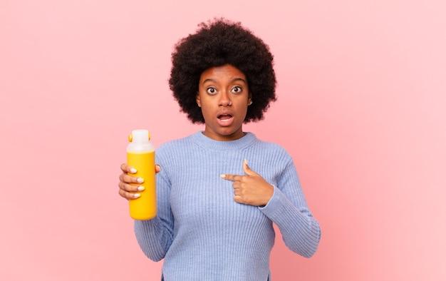 Une femme afro a l'air choquée et surprise avec la bouche grande ouverte, pointant vers soi. concept de smoothie