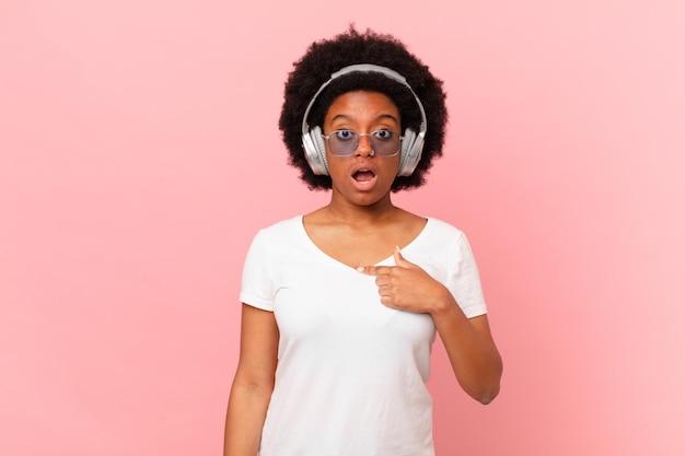 Une femme afro a l'air choquée et surprise avec la bouche grande ouverte, pointant vers soi. notion de musique