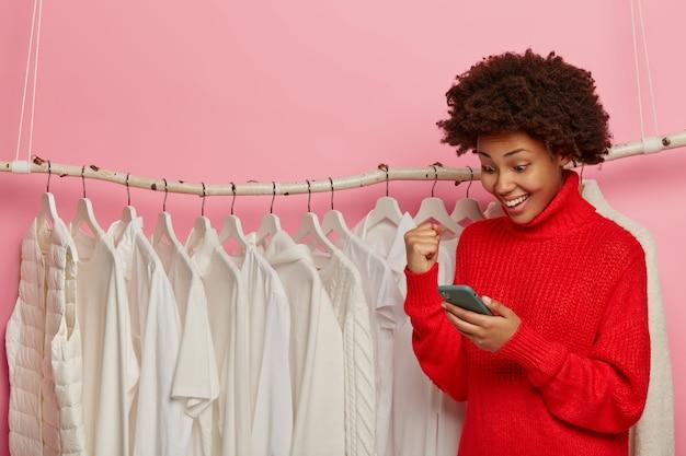Une femme afro-américaine acclame quelque chose avec le poing fermé, regarde positivement le smartphone, pose contre des tringles à vêtements avec des tenues blanches sur des cintres, fait du shopping en boutique