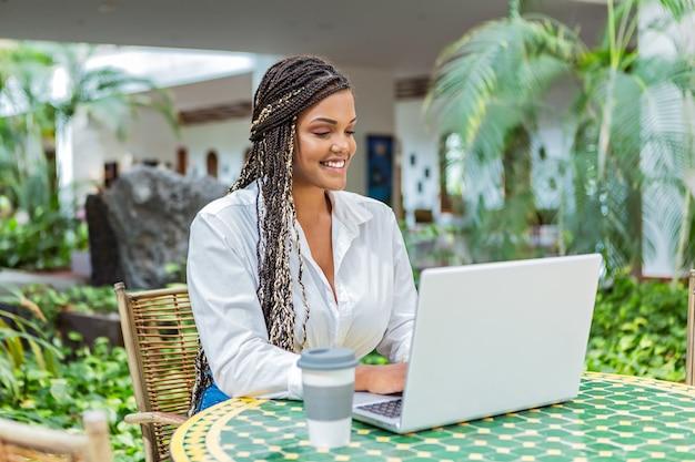 Femme afro-américaine adulte utilisant un ordinateur portable dans un café à l'extérieur avec un arrière-plan flou de plantes et de vert. femme avec des tresses assises utilisant un ordinateur portable et buvant du café.