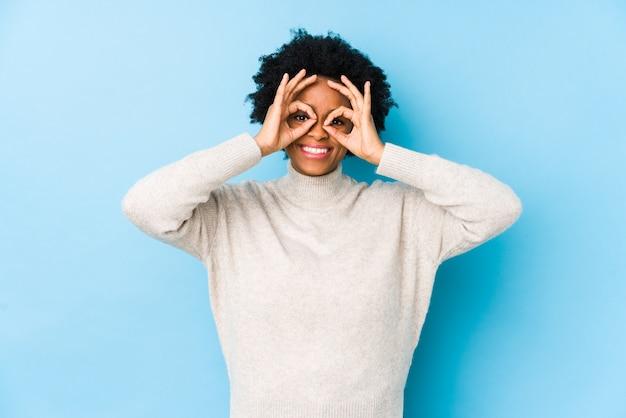 Femme afro-américaine d'âge moyen sur un bleu isolé montrant bon signe sur les yeux