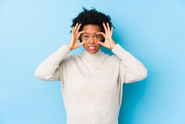 Femme afro-américaine d'âge moyen contre un bleu isolé gardant les yeux ouverts pour trouver une opportunité de succès.