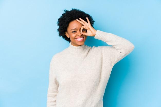 Femme afro-américaine d'âge moyen contre un mur bleu excité en gardant le geste ok sur les yeux.