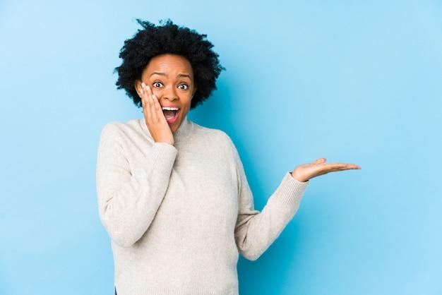 Femme afro-américaine d'âge moyen contre un mur bleu isolé détient un espace de copie sur une paume, gardez la main sur la joue. etonné et ravi.