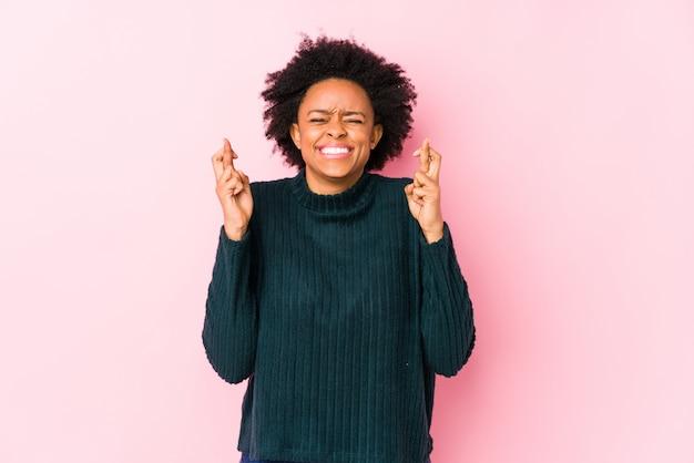Femme afro-américaine d'âge moyen contre un mur rose isolé croiser les doigts pour avoir de la chance