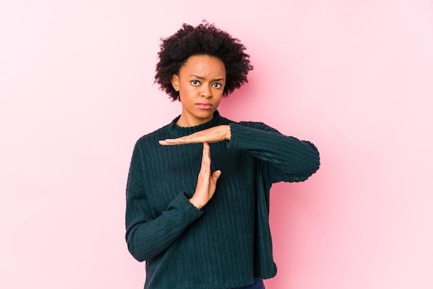 Femme afro-américaine d'âge moyen contre un mur rose isolé montrant un geste de temporisation.
