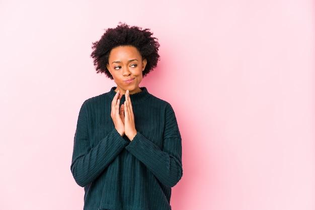 Femme afro-américaine d'âge moyen contre un mur rose isolé plan de préparation à l'esprit, la mise en place d'une idée.