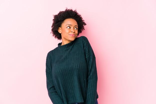 Femme afro-américaine d'âge moyen contre un mur rose isolé rêvant d'atteindre les buts et objectifs