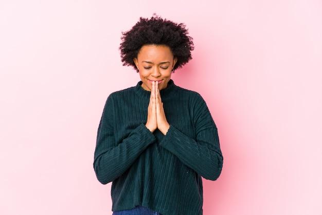 Femme afro-américaine d'âge moyen contre un mur rose isolé tenant par la main dans la prière près de la bouche, se sent confiant.