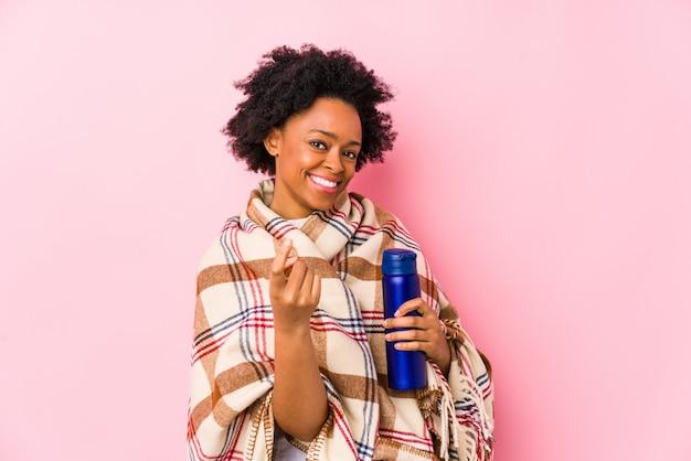 Femme afro-américaine d'âge moyen dans un camping isolé pointant avec le doigt vers vous comme si vous vous invitiez à vous rapprocher.
