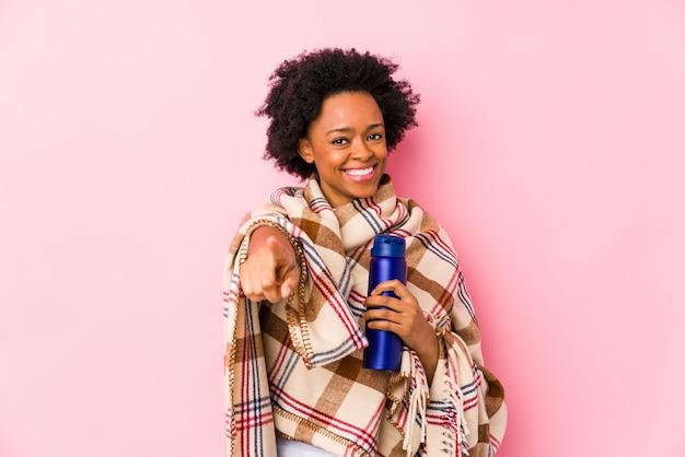 Femme afro-américaine d'âge moyen dans un camping isolé sourires joyeux pointant vers l'avant.
