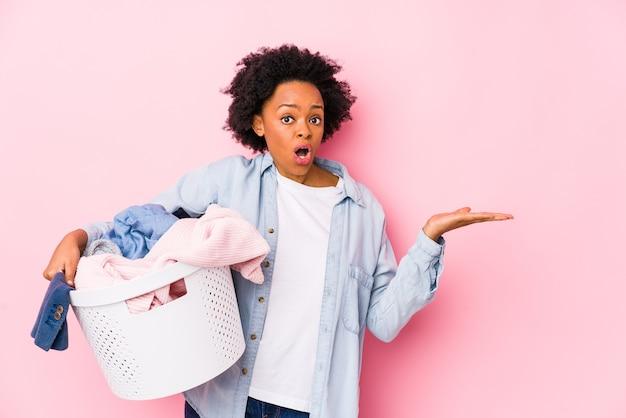 Femme afro-américaine d'âge moyen faisant la lessive isolé impressionné tenant copie espace sur la paume.