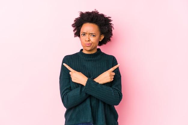 Femme afro-américaine d'âge moyen sur un rose points isolés sur le côté, essaie de choisir entre deux options.