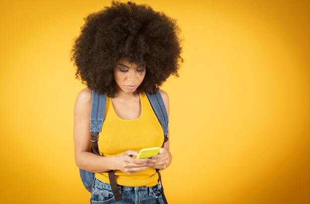 Une femme afro-américaine à l'aide de son smartphone recommande de télécharger une nouvelle application