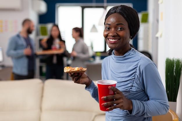 Femme afro-américaine appréciant la nourriture et les boissons après le travail avec des collègues travailleur