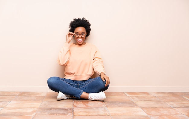 Femme afro-américaine assise sur le sol avec des lunettes et surpris