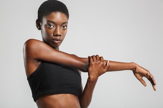 Femme afro-américaine athlétique étirant ses bras tout en travaillant isolé sur un mur blanc