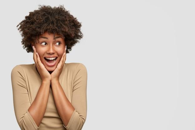 Une femme afro-américaine attrayante expressive s'exclame de bonheur, garde les mains sur les joues, regarde joyeusement de côté comme avis meilleur ami revenant de l'étranger, se tient contre un mur blanc, espace vide