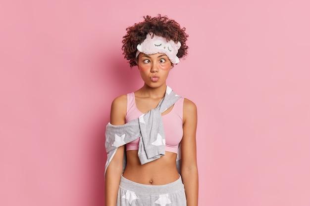 Femme afro-américaine aux cheveux bouclés assez drôle garde les lèvres pliées croise les yeux et fait une grimace drôle habillée en vêtements de nuit pose contre le mur rose