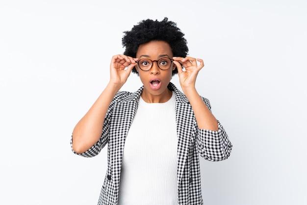 Femme afro-américaine avec blazer isolé avec des lunettes et surpris