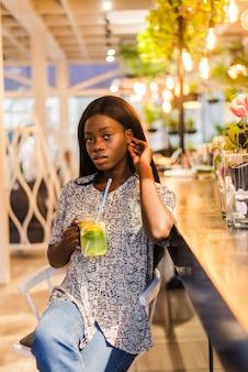 Femme afro-américaine, boire de la limonade cocktail au café au bar.