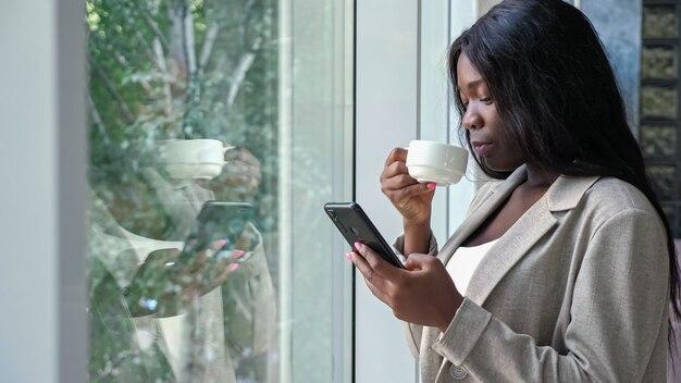 Une femme afro-américaine boit du café et des sms au téléphone