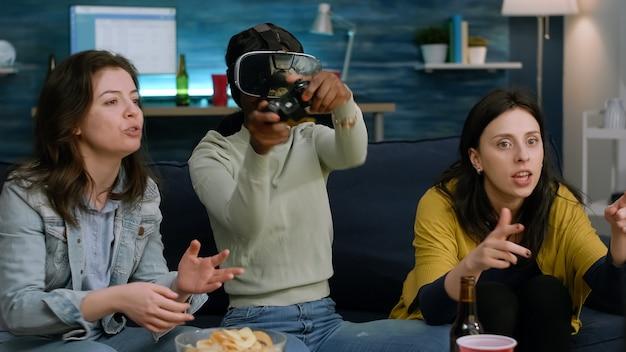 Femme afro-américaine bouleversée portant un casque de réalité virtuelle perdant des jeux vidéo en ligne à l'aide d'un contrôleur ...