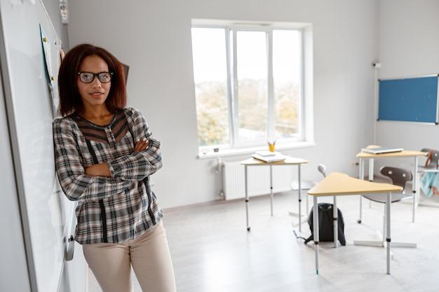 Femme afro-américaine avec les bras croisés debout dans la salle de classe