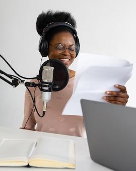 Femme afro-américaine avec un casque et un microphone enregistrant un podcast dans un studio d'enregistrement