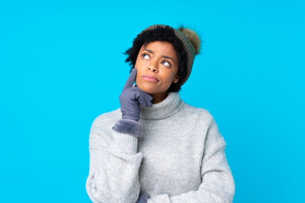 Femme afro-américaine avec chapeau d'hiver sur un mur bleu isolé