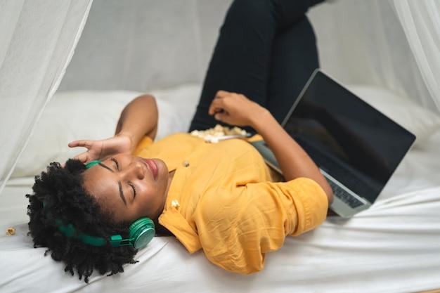 Femme afro-américaine en chemise jaune écoutant de la musique avec ses écouteurs dans le salon